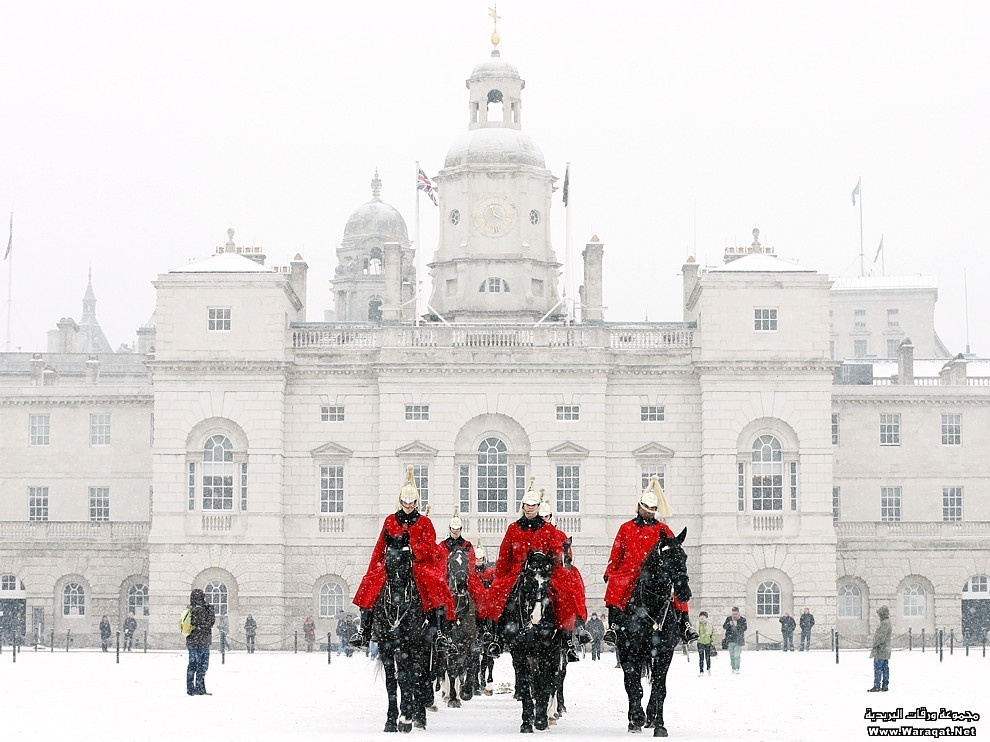 Members of the Household Cavalry Mounted Regiment cross Horse Guards Parade in the snow in central London
