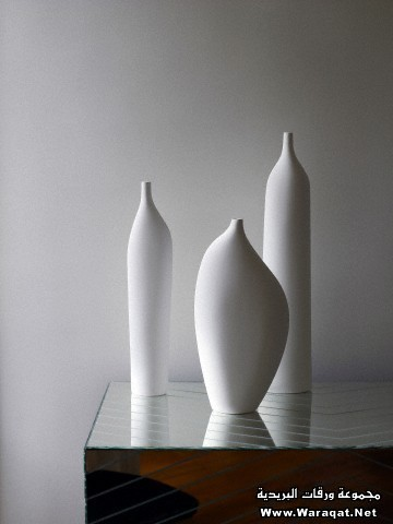 Three white porcelain vases on mirrored sideboard in French apartment.