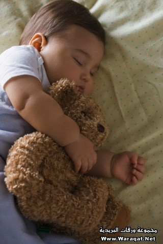 Mixed race baby boy sleeping with teddy bear