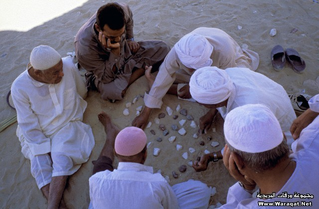 Arab Republic of Egypt, Libyan Desert, Farafra oasis, Group of men sitting on the sand and playing with stones