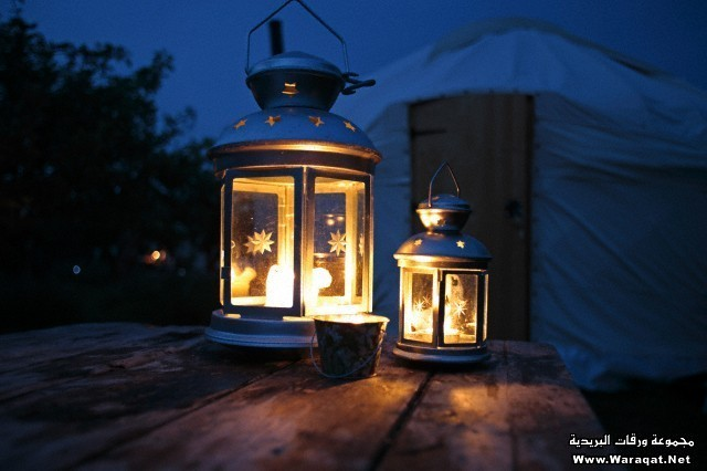 England, Isle of Wight. Candle lanterns on a table with a yurt in the background; Island Yurts near Freshwater Bay.