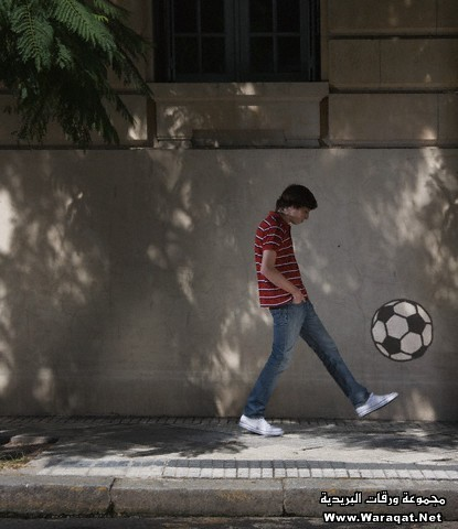 Young man kicking a graffiti soccer ball