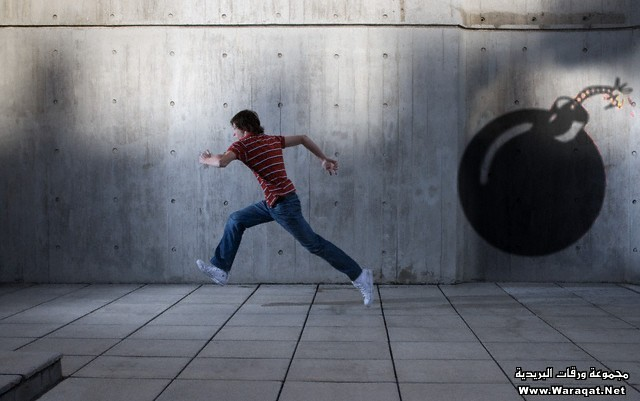 Young man running from a graffiti bomb