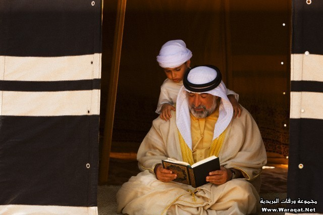 Arab man sitting in tent and reading the Holy Quran