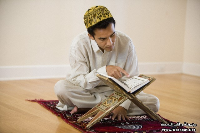 A Muslim Man Reading Koran on a Prayer Mat