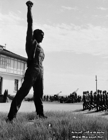 Soldiers Marching Past a Bronze Statue