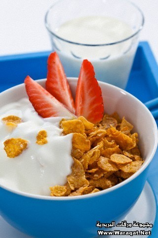 Bowl of cornflower with strawberries and glass of milk on white background