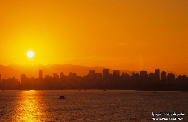 Vancouver Skyline and the Coast Mountains from Kitsilano Beach at Sunrise, Vancouver, British Columbia, Canada.