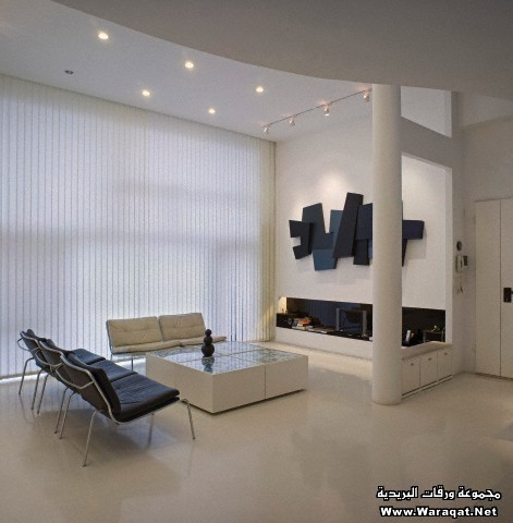 White apartment, Beijing, arranged on four floors, designed by Zhang Zi Hui and Chen Yi Lang. Living room with marble-topped table in four sections and recessed low alcove for the television and books