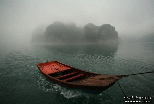 A red skiff is towed with one of the many limestone islands of Halong Bay in the background. Vietnam. 2006.